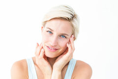 Happy blonde smiling at camera with hands on cheeks Stock Images