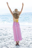 Happy blonde standing by the sea arms raised Royalty Free Stock Images