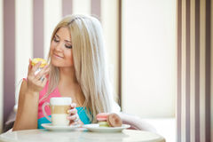 Happy blonde at a table in a cafe Stock Photos