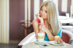 Happy blonde at a table in a cafe Stock Photo