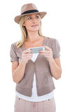 Happy blonde in trilby holding phone Stock Photography