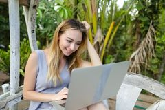 Happy blonde using laptop and sitting in exotic garedn with palms in background. stock photos