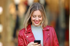 Happy blonde using a smart phone in a mall. Front view portrait of a happy blonde using a smart phone in a mall Royalty Free Stock Images