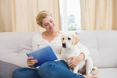 Happy blonde using tablet pc with puppy Stock Photo