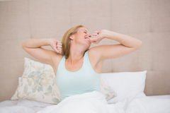 Happy blonde waking up in bed Royalty Free Stock Image