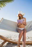 Happy blonde wearing sunhat sitting on hammock reading book Stock Photos