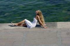 Happy blonde in white near sea on pier Stock Image