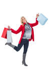 Happy blonde in winter clothes holding shopping bags Royalty Free Stock Photos