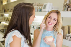 Happy blonde woman applying cosmetic products Stock Photo