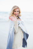 Happy blonde woman in a blanket waving at the camera Royalty Free Stock Photos
