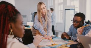 Happy blonde woman boss leading multiethnic development company employees, working together on building plan in office. Business partners cooperate and work as stock video footage