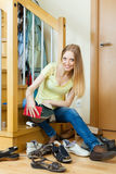 Happy blonde woman cleaning footwear Royalty Free Stock Images