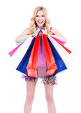 Happy blonde woman with colored shopping bags. Royalty Free Stock Images