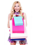 Happy blonde woman with colored shopping bags. Stock Photos