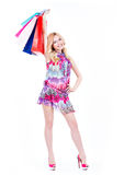 Happy blonde woman with colorful shopping bags. Royalty Free Stock Images