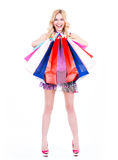 Happy blonde woman with colorful shopping bags. Royalty Free Stock Photography