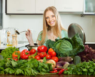 Happy blonde woman cooking with heap of  vegetables Royalty Free Stock Photos