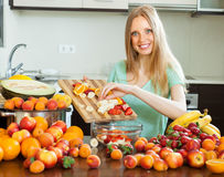 Happy blonde woman cooking with ripe fruits Royalty Free Stock Photography