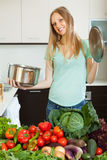 Happy blonde woman with cooks pan Royalty Free Stock Image