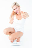 Happy blonde woman crouching on a scales with thumbs up. On white background Royalty Free Stock Images