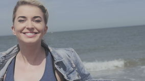 Happy blonde woman in denim jacket sending a kiss on lonely beach. stock video