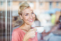 Happy blonde woman drinking a cup of coffee Royalty Free Stock Photography