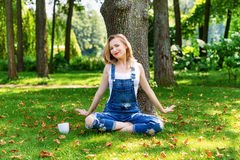 Happy blonde woman enjoying nature sitting on green grass with cup of coffee. Freedom concept Stock Images