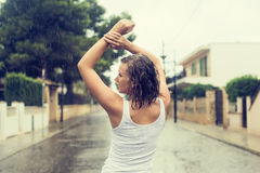 Happy blonde woman enjoying tropical rain. Royalty Free Stock Photo