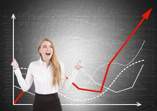 Happy blonde woman and graphs on chalkboard stock images