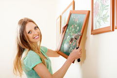 Happy Blonde Woman Hanging Picture With Flowers Royalty Free Stock Images