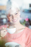 Happy blonde woman holding a cup of coffee Royalty Free Stock Images
