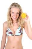 Happy blonde woman holding orange Stock Photography