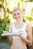 Happy blonde woman holding plate with herbal medicine Stock Photo