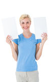 Happy blonde woman holding sheets of paper Royalty Free Stock Photos
