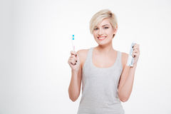 Happy blonde woman holding toothbrush and toothpaste Stock Photography