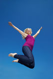 Happy blonde woman jumping high Stock Photography
