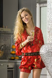 Happy blonde woman in the kitchen. Happy woman wearing red dress with glass of champagne in a kitchen Royalty Free Stock Image