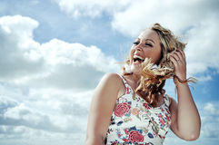 Happy blonde woman laughing in the wind on the background of blue sky. Royalty Free Stock Image
