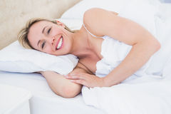Happy blonde woman lying in bed Royalty Free Stock Photos