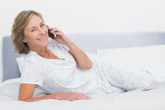 Happy blonde woman lying on bed making a phone call. Smiling at camera in bedroom at home Stock Images