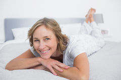 Happy blonde woman lying on bed Stock Photography