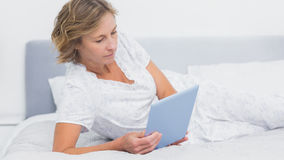Happy blonde woman lying on bed using tablet pc Stock Image