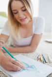 Happy blonde woman lying on floor sketching on paper Stock Photo