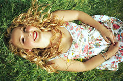 Happy blonde woman lying on grass. Royalty Free Stock Image