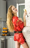 Happy blonde woman in the modern kitchen. Happy woman wearing red dress with glass of champagne in a kitchen Stock Images