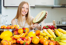 Happy blonde  woman  near heap of fruits at home kitchen Stock Photos