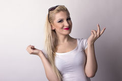 Happy blonde woman over a grey background Royalty Free Stock Photos