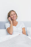 Happy blonde woman on the phone in bed smiling at camera Stock Photos