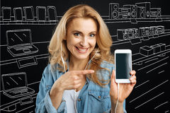 Happy blonde woman pointing at her smartphone Stock Photography
