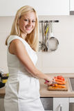 Happy blonde woman preparing vegetable Royalty Free Stock Photos